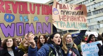 """Ukrainian feminists hold placards reading """"Revolution is a woman"""" and """"Enough to cover inequality with traditions"""" during a march on March 8, 2017 in Kiev, as part of International Women's Day. / AFP PHOTO / Sergei SUPINSKY"""