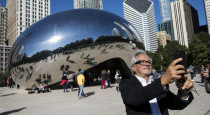 "Anish Kapoor, creator of Cloud Gate, aka ""The Bean,"" takes a selfie in front of the famous sculpture in Millennium Park, Tuesday, Oct. 17, 2017. 