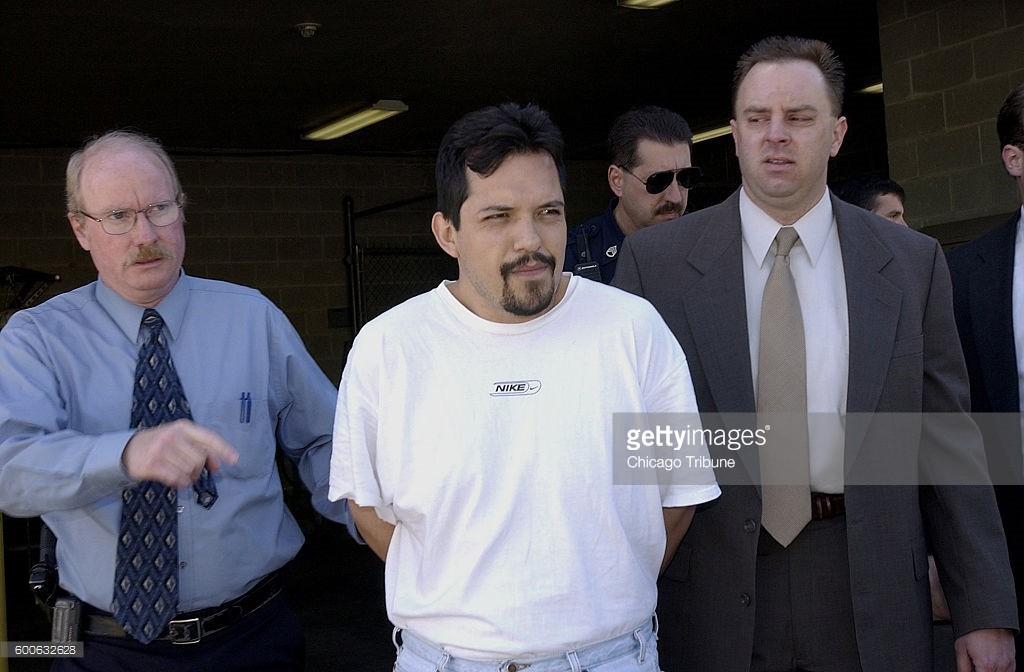 Palatine police walk Brown's Chicken murder suspect Juan A. Luna Jr., center, to a squad car for transport from the Palatine police station on May 18, 2002. (John Dziekan/Chicago Tribune/TNS)