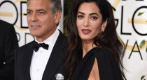 """Actor George Clooney (L), wearing a """"Je suis Charlie"""" button,  and Amal Clooney arrive on the red carpet for the 72nd annual Golden Globe Awards, January 11, 2015 at the Beverly Hilton Hotel in Beverly Hills, California. AFP PHOTO / MARK RALSTON        (Photo credit should read MARK RALSTON/AFP/Getty Images)"""
