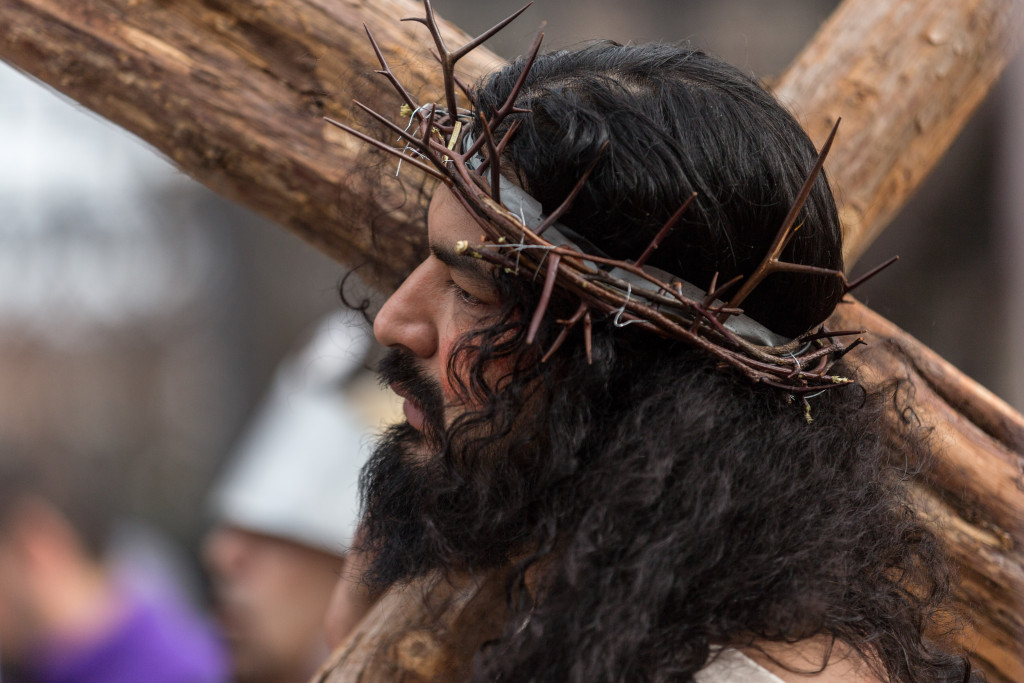 Jesus, portrayed by Anthony Macias, carries a cross during Pilsen Via Crucis.   Erin Brown/Sun-Times