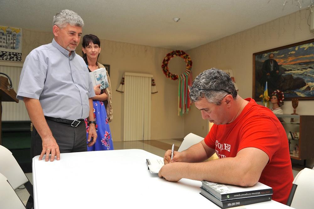 В.Кіпіані підписує книжку о. Василеві Петрову